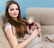 Beautiful pregnant woman. Sitting on the sofa and hold toy in hands Stock Image