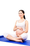 Beautiful pregnant woman sitting on a yoga mat Royalty Free Stock Images