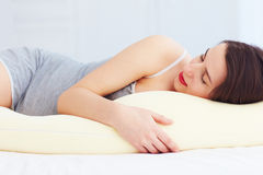 Beautiful pregnant woman sleeps comfortable with tummy supporting pillow Royalty Free Stock Photos