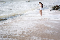 Beautiful pregnant woman stand on the sea shore Stock Image