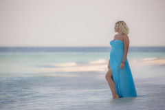 Beautiful pregnant woman is standing on the amazing beach Stock Photography