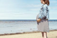 Beautiful pregnant woman standing on the beach. Pregnant woman taking a walk by the beach royalty free stock photos