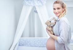 Pregnant woman in child`s room Royalty Free Stock Photo