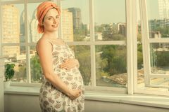 Beautiful pregnant woman standing near a large open window. Happy smiling woman while pregnancy at home. She is wearing a romantic sundress and turban and royalty free stock photography