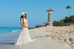 Beautiful pregnant woman standing on a sandy beach with palm trees on a lighthouse background. Caribbean Sea. Stock Photography