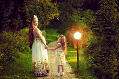 Beautiful pregnant woman in the summer is walking with my daught stock images