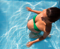 Beautiful pregnant woman sun tanning at blue pool Stock Photography
