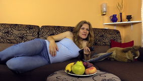 Beautiful pregnant woman switch TV channel with remote control stock video