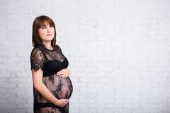Beautiful pregnant woman thinking or dreaming about something ov Royalty Free Stock Images