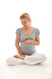 Beautiful pregnant woman thinking of her baby Stock Photo