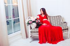 Beautiful pregnant woman touching her belly with hands in the living room Royalty Free Stock Images