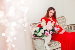 Beautiful pregnant woman touching her belly with hands in the living room having, the light give a cozy atmosphere. Waiting for baby. Woman in red royalty free stock images