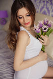 Beautiful pregnant woman with tulips waiting a Royalty Free Stock Photo