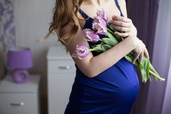 Beautiful pregnant woman with tulips waiting a Royalty Free Stock Photography