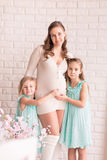 Beautiful pregnant woman with two daughters Stock Image