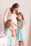 Beautiful pregnant woman with two daughters Royalty Free Stock Image