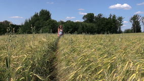Beautiful pregnant woman walk through ripe rye field in summer