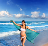 Beautiful pregnant woman walking on blue beach Stock Photos