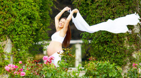 Beautiful pregnant woman walking. Pregnant woman walking on a garden holding a long white sheet against the wind Royalty Free Stock Photography