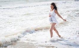 Beautiful pregnant woman walking on the sea shore Stock Photos