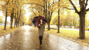 Beautiful pregnant woman walking with umbrella along autumn alley on a rainy day. Beautiful young woman walking along autumn alley Royalty Free Stock Images