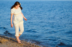 Beautiful pregnant woman walks along the shore Royalty Free Stock Photos