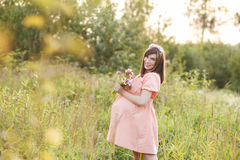 Beautiful pregnant woman walks in the par. K and holding a bouquet Stock Photo