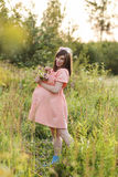 Beautiful pregnant woman walks in the park. And holding a bouquet Stock Image