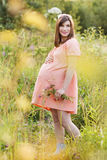 Beautiful pregnant woman walks in the park. And holding a bouquet Stock Images