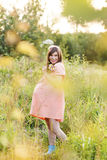 Beautiful pregnant woman walks in the park. And holding a bouquet Stock Photo