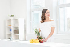 Beautiful pregnant woman washing a pineapple Stock Images