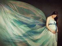 Beautiful pregnant woman in waving fabric Royalty Free Stock Images