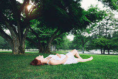 Beautiful pregnant woman in white dress on nature. Beautiful pregnant woman in white dress on nature, outdoors. Expectant mother holds hands on belly on natural Royalty Free Stock Photo