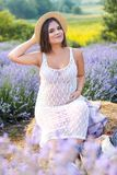 beautiful pregnant woman in white dress touching belly and straw hat at violet stock photos