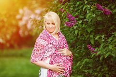Beautiful pregnant woman in white maternity dress with pink sheer scarf looking dreamy in the park near purple lilacs royalty free stock photography