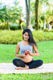 Beautiful pregnant woman yoga with apple. In the park Royalty Free Stock Photography