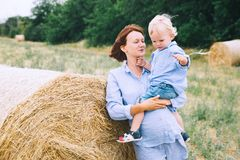 Pregnant woman and son on nature. Mother waiting of a second bab. Beautiful pregnant women and her cute toddler son having fun on wheat field with haystacks at Stock Image