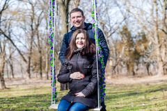 Beautiful pregnant woman and her handsome husband hugging the tummy on the swing royalty free stock photo