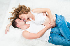 Beautiful pregnant young couple laying on top. Royalty Free Stock Photography