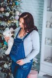 Beautiful pregnant woman in denim overalls holding a Teddy bear. A beautiful pregnant young girl in a blue denim overalls holds a bear in her hands and looks at Royalty Free Stock Photography