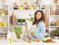 Pregnant young woman having breakfast. Beautiful pregnant young woman having breakfast at kitchen Stock Images