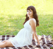 Beautiful pregnant young woman lying on the grass in summer Royalty Free Stock Photography