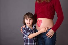 Beautiful preschool child, hugging his pregnant mom. Happily expecting to be big brother. Red heart drawn on mothers belly, child kissing her little belly stock images