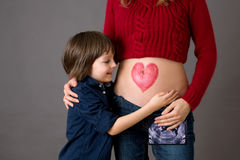 Beautiful preschool child, hugging his pregnant mom. Happily expecting to be big brother. Red heart drawn on mothers belly, child kissing her little belly stock image
