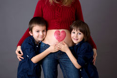 Beautiful preschool children, hugging their pregnant mom Royalty Free Stock Photo