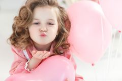 Beautiful preschool girl in a white studio with pink heart-shaped balloons royalty free stock images