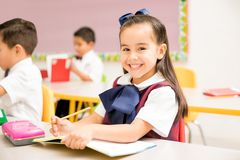 Beautiful preschool student in a classroom. Portrait of a gorgeous Latin preschool student in uniform doing a writing assigment in a classroom and smiling royalty free stock images