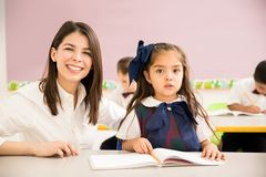 Beautiful preschool teacher and pupil. Portrait of a gorgeous Hispanic preschool teacher helping one of her students in the classroom Stock Photography