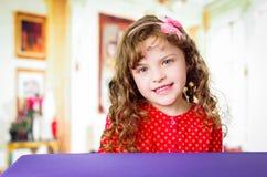 Beautiful preschooler girl sitting at the table Stock Photo