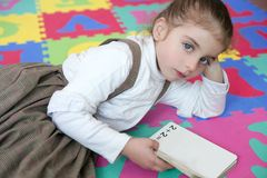 Beautiful preschooler girl studying book Royalty Free Stock Photo